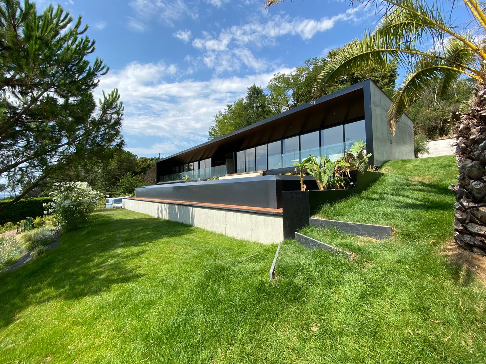 aménagement du jardin avec une piscine à débordement, une terrasse et des espaces verts à toulouse